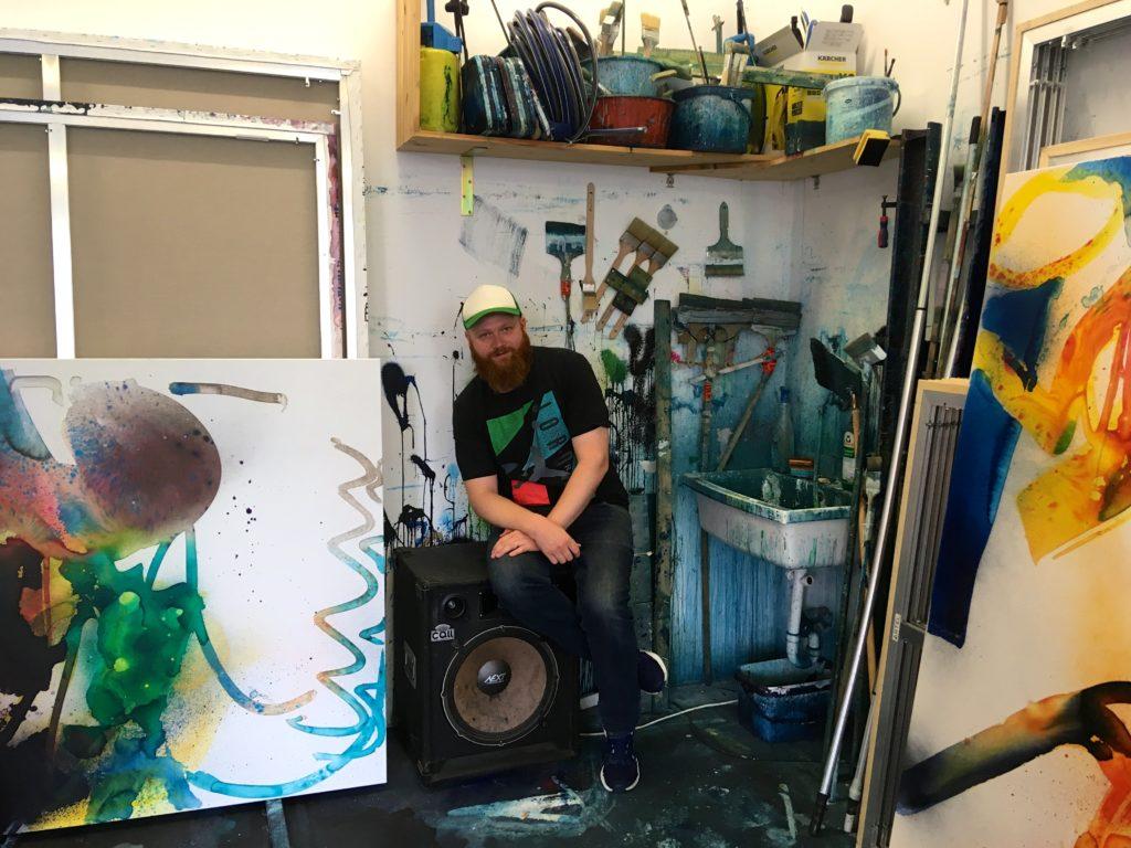 Der Maler Max Frintrop posiert neben einem Bild und seinen Arbeitsmaterialien in seinem Düsseldorfer Atelier.
