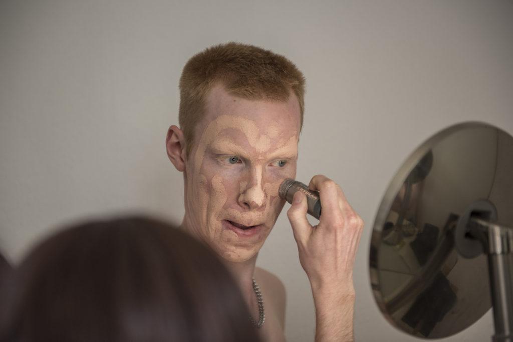 an Kollenbach schaut in den Spiegel und malt mit einem Pinsel Schichten von Make-up in sein Gesicht.