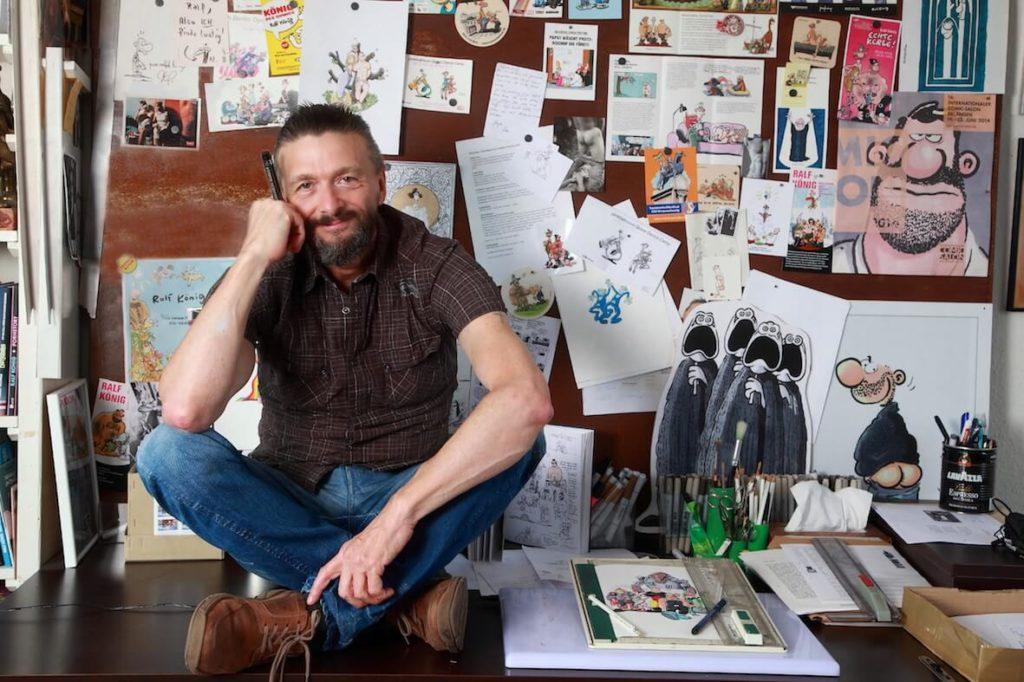 Der Comic-Zeichner Ralf König sitzt im Schneidersitz auf dem Zeichentisch seines Kölner Ateliers.
